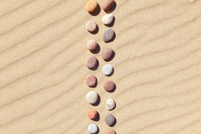 Modell av kulöra kiselstenar på ren sand Zenbakgrund, harmoni och meditationbegrepp arkivfoto