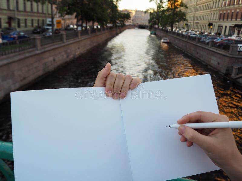 Modell av personhanden som rymmer den tomma vita anteckningsboken som förbereder sig att skriva ner hans eller hennes idéer arkivbild