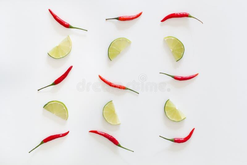Modell av skivade limefrukter och röda thai peppar för varm chili på en vit bakgrund Top besk?dar royaltyfri foto