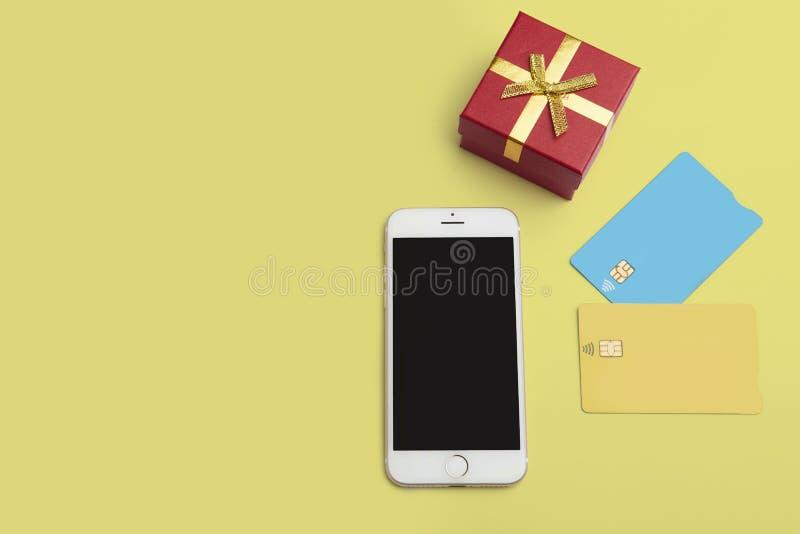 Modell av två tomma färgkreditkortar, smartphone, gåvaask på det tomma gula skrivbordet Affärsmodellbakgrund för royaltyfri fotografi