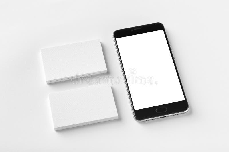 Modell av två tomma horisontalaffärskort och den svarta mobiltelefonen på vit texturerat papper fotografering för bildbyråer