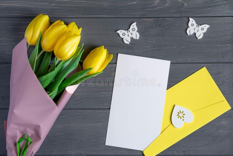 Modell, das Schablone mit Tulpenblumen, -umschlag und -buchstaben beschriftet Hintergrund für einen Glückwunschblogposten mit Blu stockbilder