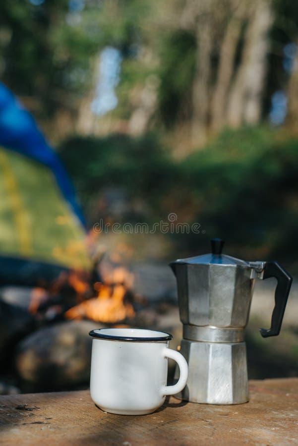 Modell der Metallkampierenden Aluminiumschale oder des Bechers und der Kaffeemaschine nahe Feuer auf Hintergrundzelt Konzeptabent lizenzfreie stockfotos