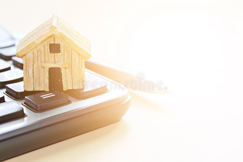 Modell des hölzernen Hauses auf Taschenrechner lizenzfreie stockfotografie