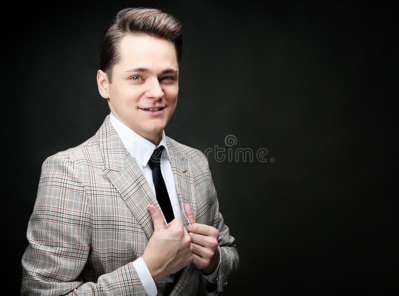 Modell des jungen Mannes, das über dunklem Hintergrund aufwirft lizenzfreies stockbild