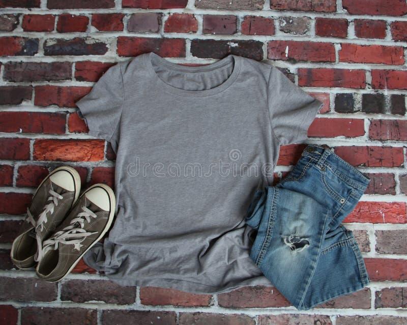 Modell-Ebenen-Lage des grauen T-Shirts lizenzfreie stockfotos