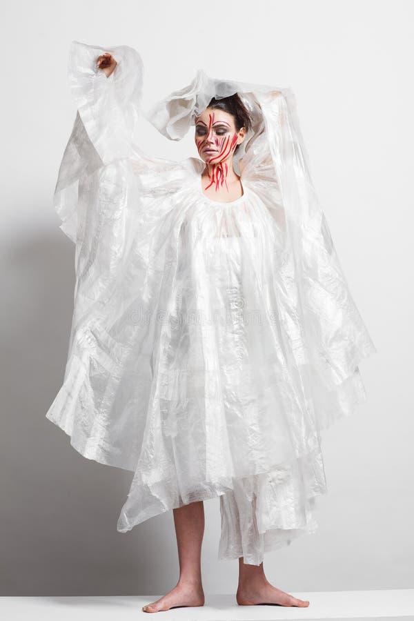 Modell in einem Regenmantel hergestellt vom Zellophan und im kreativen Make-up stockbilder
