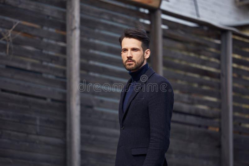 Modell för affär för modeskäggstil som stilig manlig poserar i stil som utomhus beklär det blåa omslaget och byxa på gataträvägge fotografering för bildbyråer