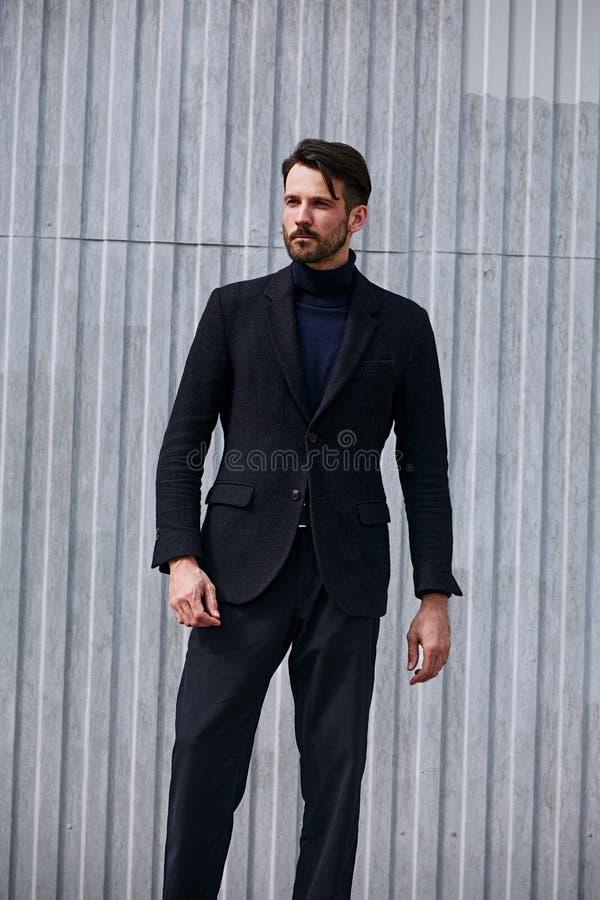 Modell f?r aff?r f?r modesk?ggstil som stilig manlig poserar i stil som utomhus bekl?r det bl?a omslaget och byxa p? gatav?ggen royaltyfri foto