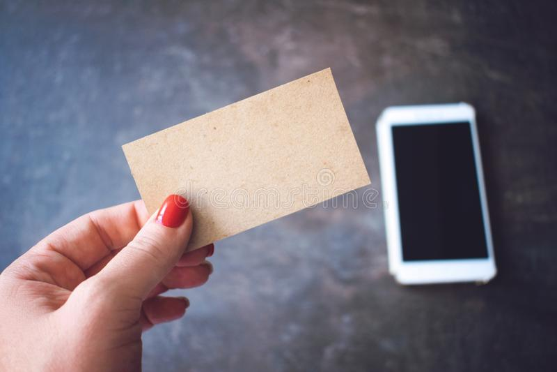 Modell för affärskort Kvinnor räcker att rymma det pappers- tomma affärskortet på defocused smartphone- och anteckningsbokbakgrun royaltyfria foton