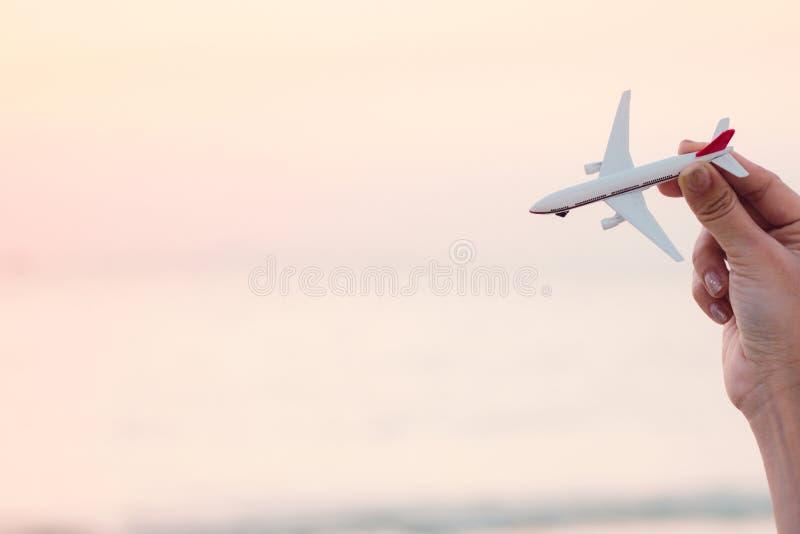 Modell för flygplan för kvinnahand hållande i solnedgånghimmel och sommarhav b royaltyfri foto