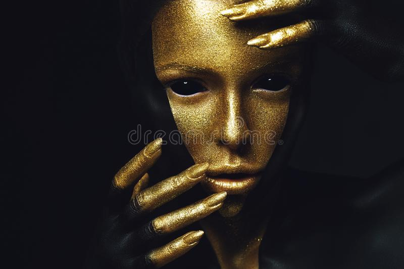 Modell för högt mode med svart och guld- läder, guld- fingrar royaltyfri bild