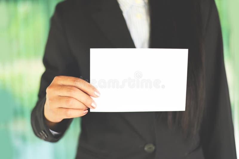 Modell för hand för affärskvinna som rymmer det tomma arket av papperskontoret som arbetar - den unga kvinnan i dräkt visar vitt  arkivfoton