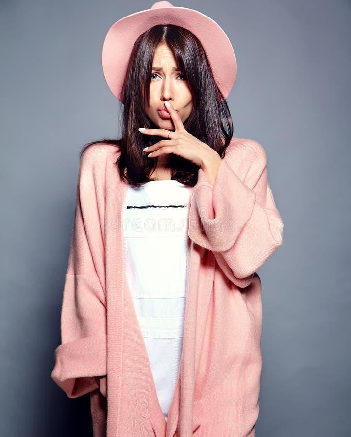 Modell för Hipsterbrunettkvinna i stilfull rosa överrock och färgrik hatt royaltyfri foto