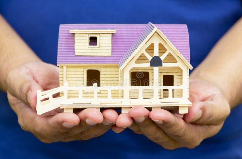 Modell för maninnehavhus i hans hand Begreppet av konstruering arkivfoto