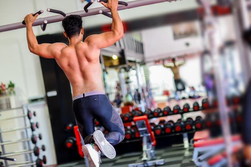 Modell för muskulös kondition för idrottsman nen som manlig drar upp på horisontalstång royaltyfria foton