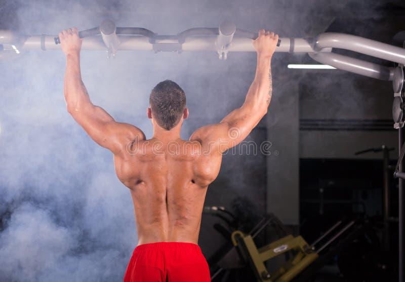 Modell för muskulös kondition för idrottsman nen som manlig drar upp på horisontalstång i en idrottshall arkivbild