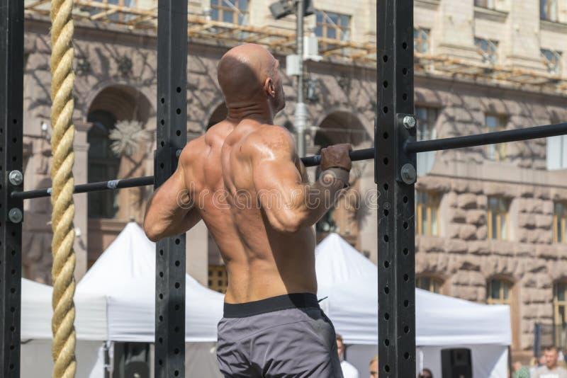 Modell för muskulös kondition för idrottsman nen som manlig drar upp på horisontalstång i en idrottshall Closeup av den starka id arkivbilder