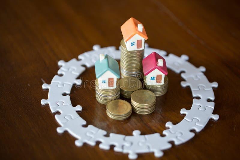 Modell för tre hus på buntmynt Pussel, sparande pengar och egenskapsledningbegrepp, investeringegenskap, hem- försäkring royaltyfri bild