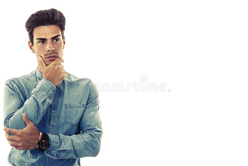 Modell för ung man på vit Tvivel och bryderi Fritt tomt sidoutrymme royaltyfri foto