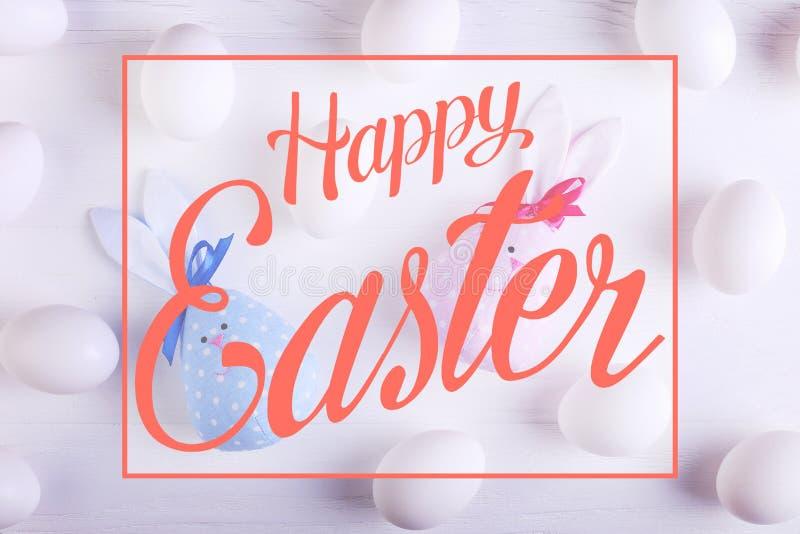 Modell för vita ägg, inklusive handgjord kanin för påsk två, blått och rosa Text lyckliga easter arkivbilder