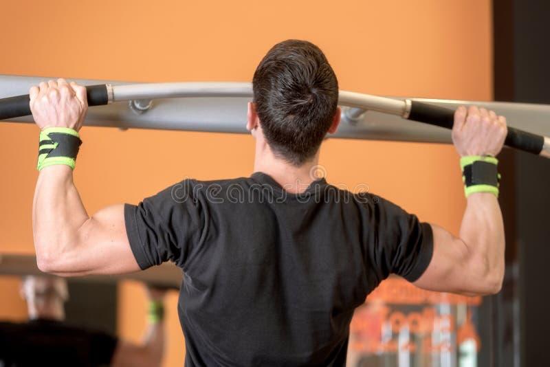 Modell f?r muskul?s kondition f?r idrottsman nen som manlig drar upp p? horisontalst?ng i en idrottshall arkivbild