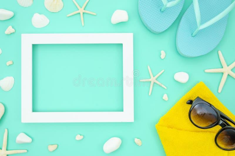Modell f?r sommarstrandram med sj?stj?rnan och sn?ckskal Lägenheten lägger med en strandhandduk, solglasögon och bläddrar misslyc royaltyfri foto