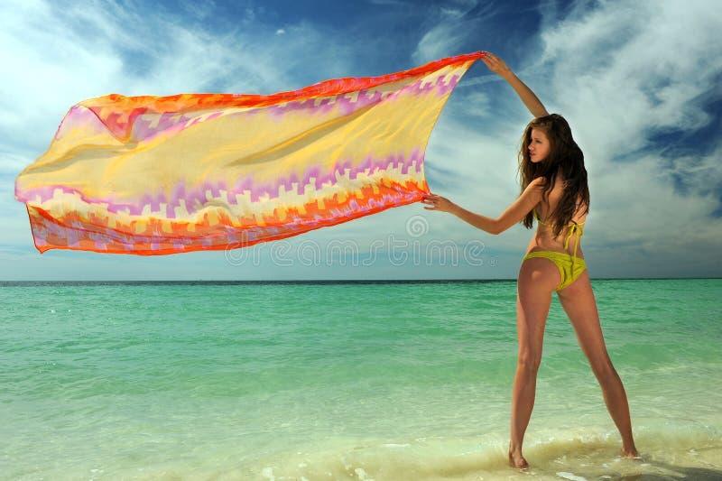 Modell i hållande pareo för gul bikini royaltyfri foto