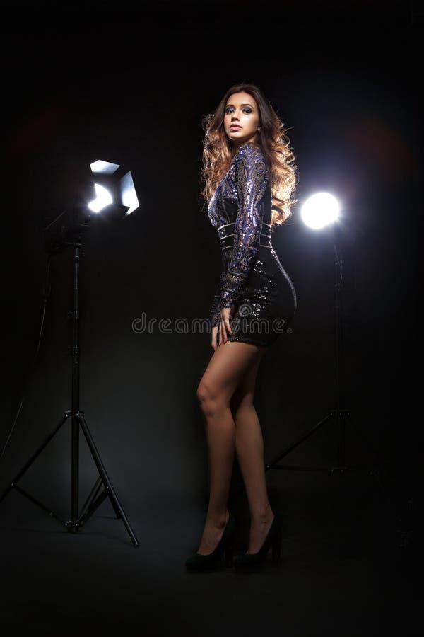 Modell i klänningen som framme poserar av kamera arkivfoto