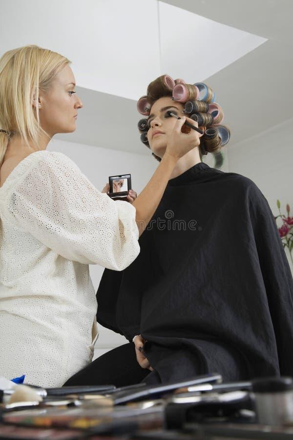 Modell i papiljotter som har makeup att appliceras royaltyfria bilder