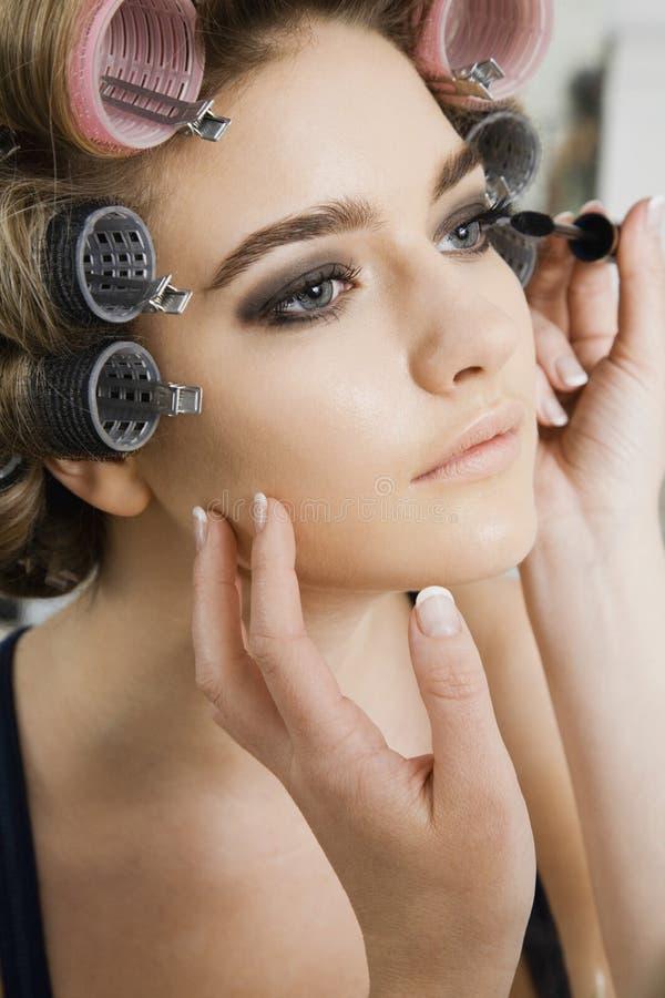 Modell i papiljotter som har makeup att appliceras royaltyfria foton