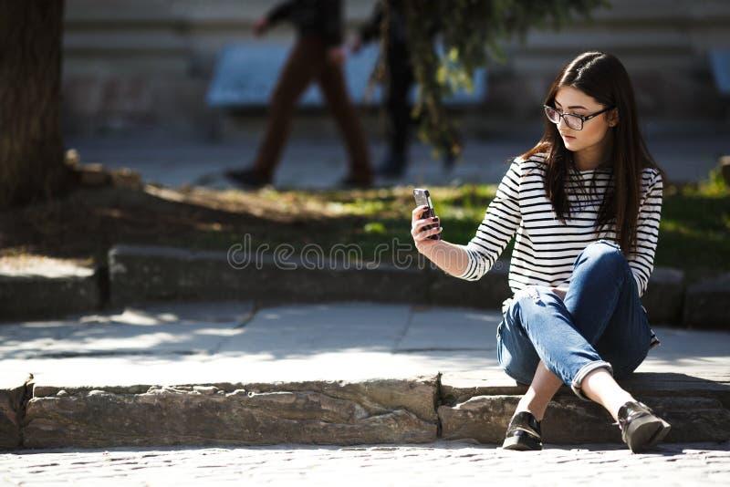 Modell i staden med telefonen arkivfoton