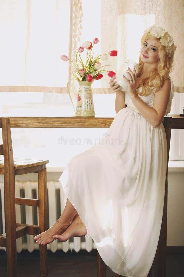 Modell kvinna, blondin som är gravid i inre royaltyfria foton