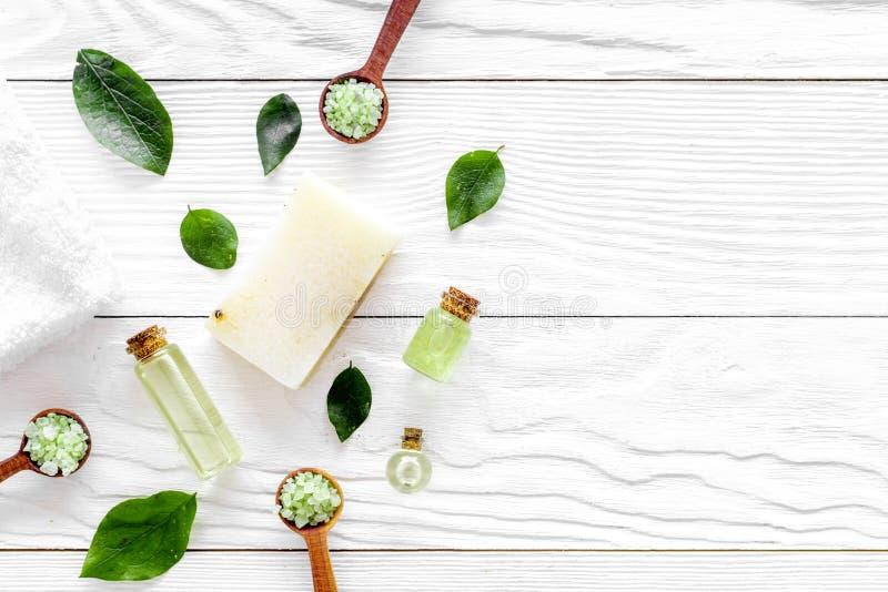 Modell med brunnsortskönhetsmedel med salt för för teträdolja och bad på grå träcopyspace för bästa sikt för bakgrund royaltyfri fotografi