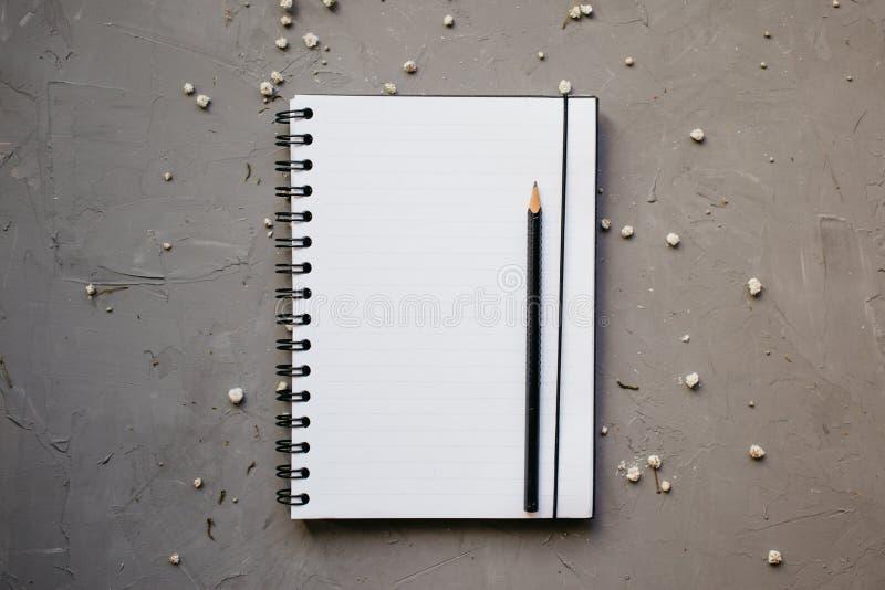 Modell med den rena notepaden och små vita blommor, bästa sikt Lägenheten lägger av den tomma anteckningsboken och blyertspennan, arkivfoto