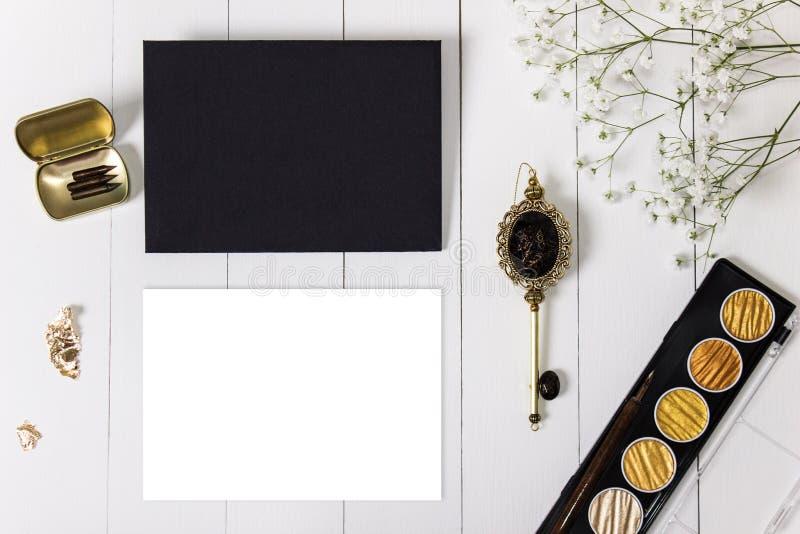 Modell med kuvertet, det tomma kortet för guld- färgpulver och blommor arkivbild