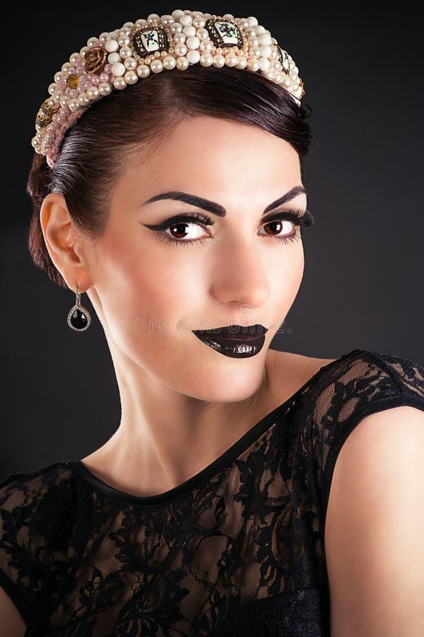 Modell med svart makeup och diademen arkivfoton