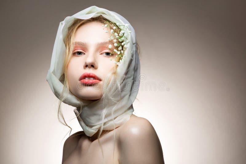 Modell mit dem ?berraschen des zarten Makes-up, das mit Blumen im Haar aufwirft lizenzfreies stockfoto