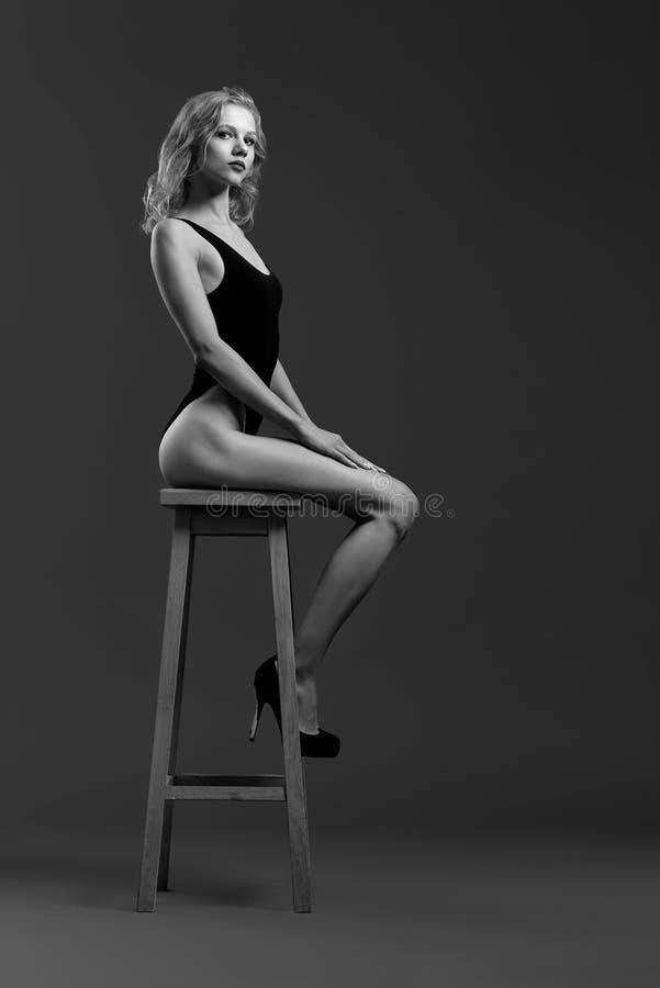 Modell mit dem perfekten Körper, der auf dem Hochstuhl, werfend sitzt auf stockfotos