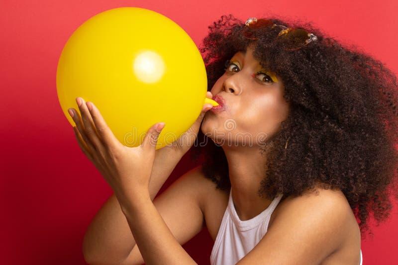Modell mit einer üppigen Frisur bläst einen Ballon auf stockfotos