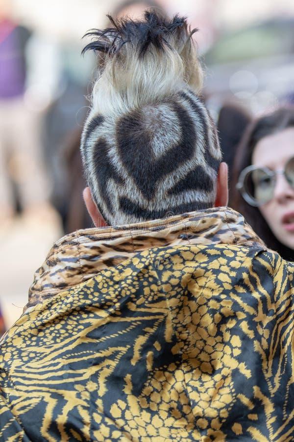 Modell mit einer ursprünglichen Frisur, die eine beschmutzte Jacke trägt stockfotografie