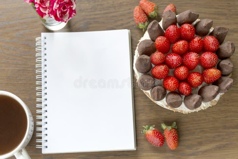 Modell mit leerem Notizblock, Tasse Kaffee und Kuchen Kleiner rosafarbener Blumenstrauß Erdbeere- und Schokolade frash Bäckerei stockbild