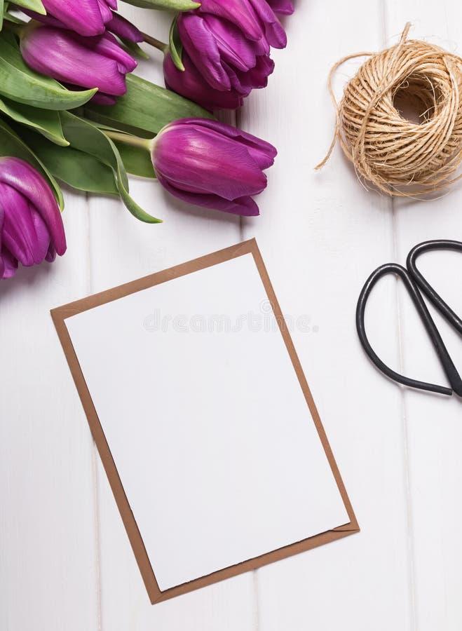 Modell mit Tulpen des leeren Papiers und des Purpurs auf der weißen Tabelle lizenzfreie stockfotografie