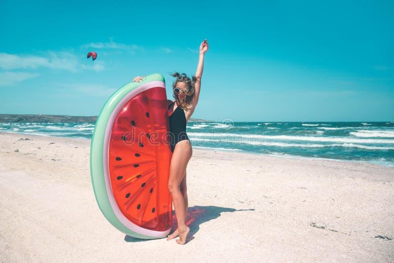 Modell mit Wassermelone lilo am Strand lizenzfreie stockfotografie