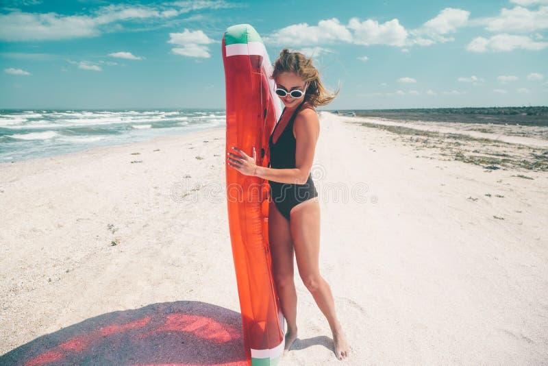 Modell mit Wassermelone lilo am Strand lizenzfreie stockfotos