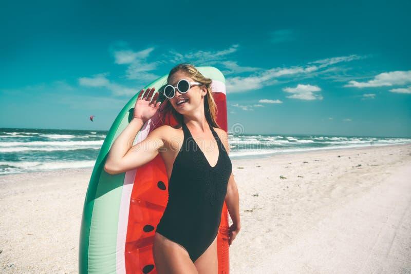 Modell mit Wassermelone lilo am Strand lizenzfreies stockbild
