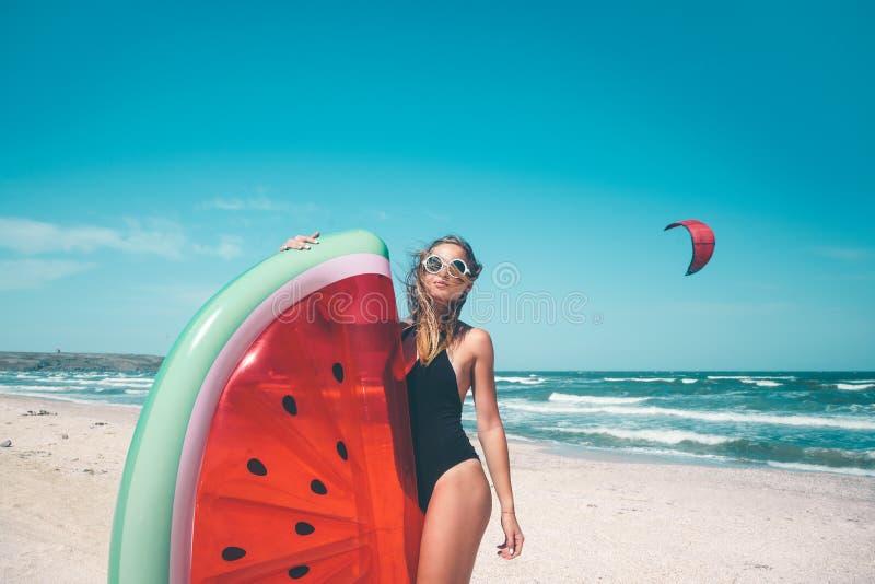 Modell mit Wassermelone lilo am Strand stockfoto