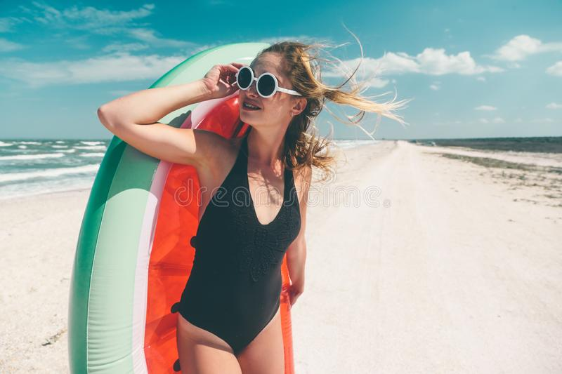 Modell mit Wassermelone lilo am Strand stockbild