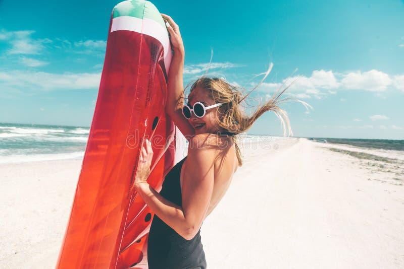 Modell mit Wassermelone lilo am Strand stockfotografie