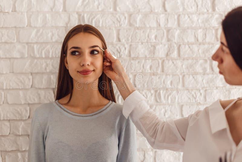 Modell- och makeupkonstnären gör en ny form naturliga ögonbryn arkivfoton